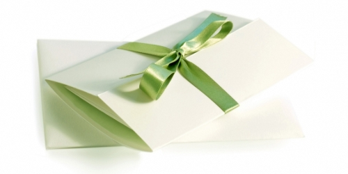 a simple and elegant wedding invitation tied with a green silk ribbon