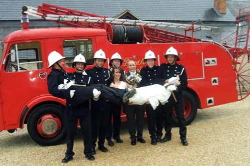 Wedding couple pose in front of classic red fire engine