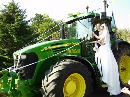 Wedding couple posing on a tractor