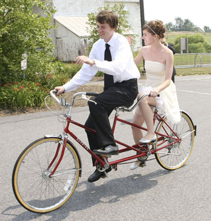 Married couple riding tandem bicycle